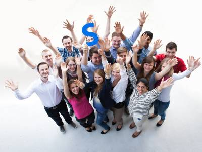"""Eine Gruppe Menschen mit ausgestreckten Armen wird von oben betrachtet, einer hält ein blaues """"S"""" in die Bildmitte."""