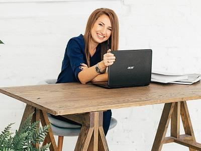 Eine Frau, die mit einem Laptop an einem Tisch sitzt und in die Kamera lächelt.