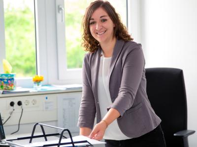 Eine Studentin, welche an einem Schreibtisch steht und in die Kamera lächelt