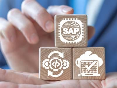 Eine Hand mit drei Holzklötzen, auf denen SAP zu lesen ist