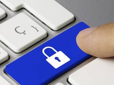 Finger, der auf Mac-Tastatur eine Taste mit Schlosssymbol drückt