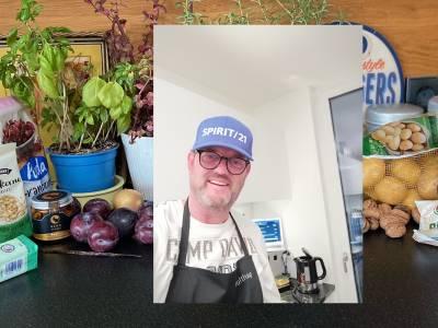 Ein lächelnder Mann mit Kochschürze, Hintergrund: ein Berg Kochzutaten