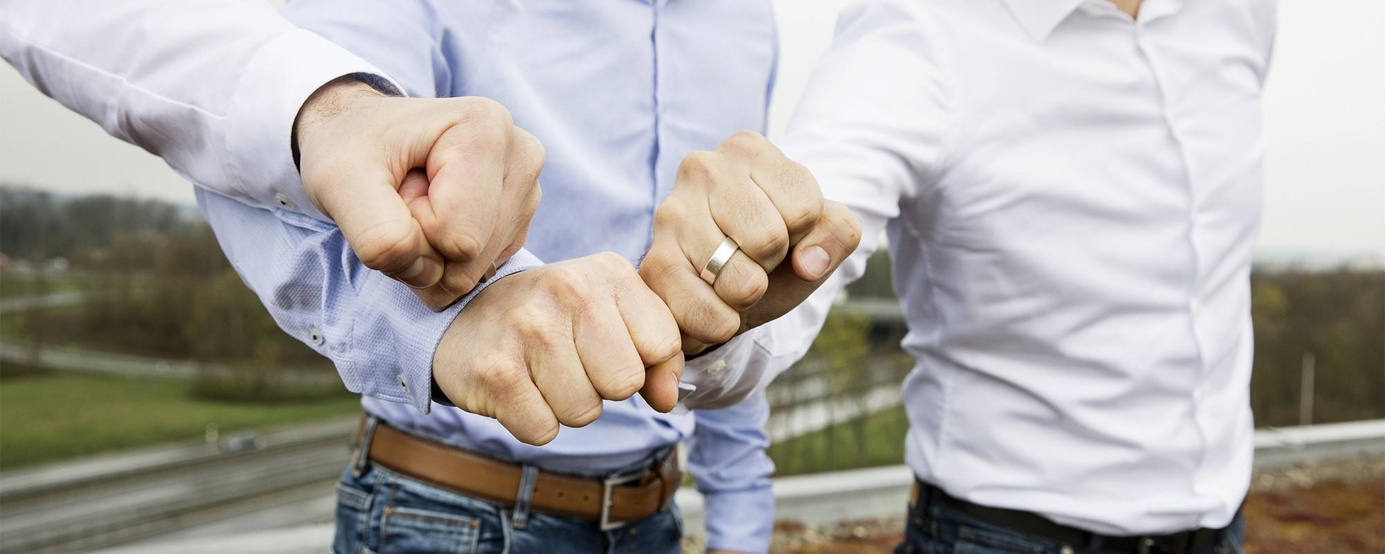 3 geballte Fäuste, eine davon mit Ehering, treffen sich