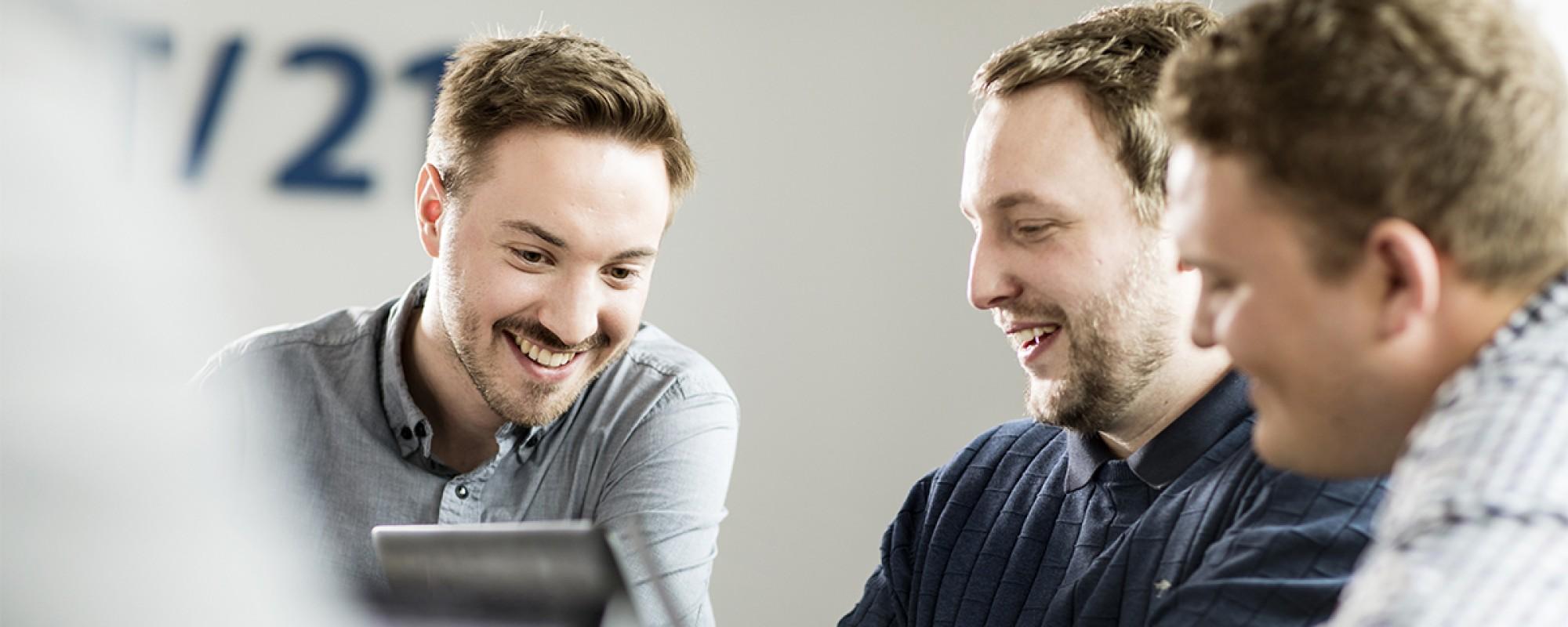 Drei Menschen, welche in einem Konferenzraum ein Meeting vor einem iPad halten.