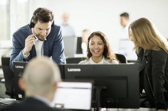 Drei Menschen arbeiten zusammen an einem Schreibtisch.